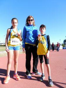 Els medallistes alevins del CA Safor, Julia Estruch i Xavi Cabanilles, amb la seua entrenadora, Montse Climent.