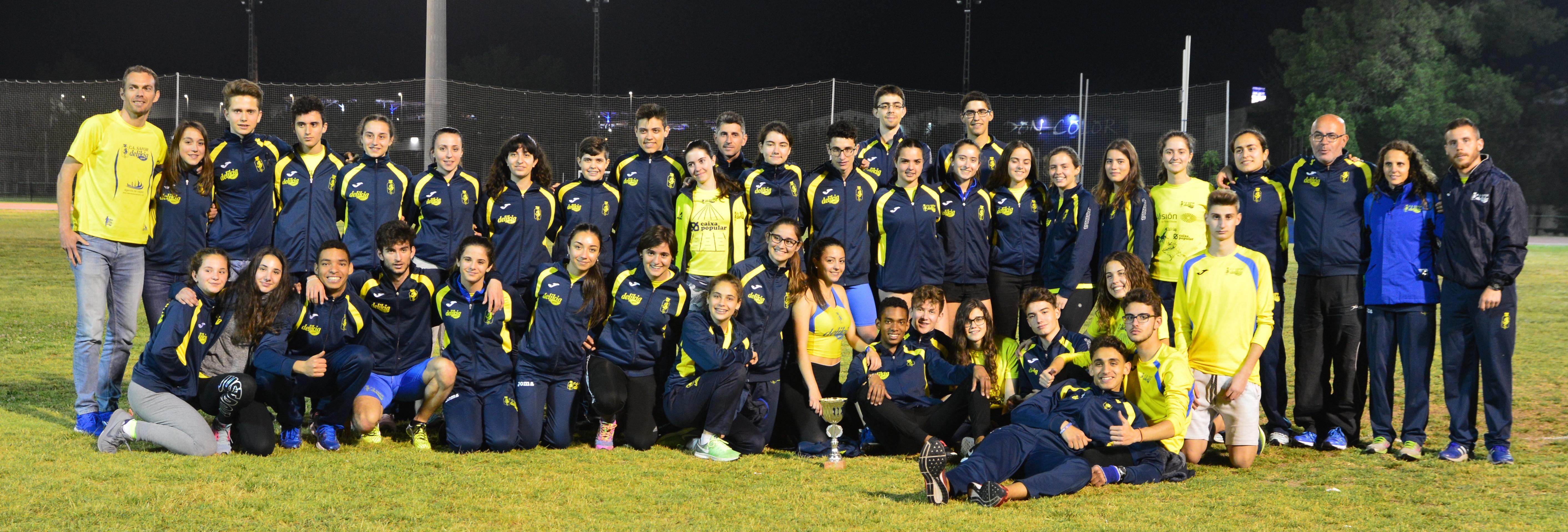 El grup d'atletes 'groguets' amb els seus entrenadors, dissabte passat a la pista de Gandia, després del provincial.